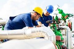 Dos trabajadores petroquímicos que examinan las válvulas de presión en un depósito de gasolina fotos de archivo libres de regalías