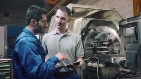 Dos trabajadores que discuten un proyecto delante de la m?quina del torno del CNC metrajes