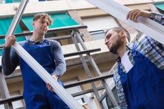 Dos trabajadores que entregan perfiles del PVC Imágenes de archivo libres de regalías