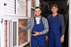 Dos trabajadores que examinan ventanas Fotografía de archivo libre de regalías