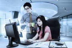 Dos trabajadores que trabajan con el gráfico virtual imagen de archivo