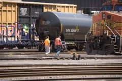 Dos trabajadores se acercan a la plataforma para el transporte de líquidos tales como petróleo diesel o crudo foto de archivo libre de regalías