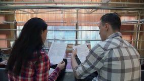 Dos trabajadores se sientan en piso y discuten el contrato dentro almacen de video