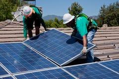 Dos trabajadores solares de sexo masculino instalan los paneles solares imagenes de archivo