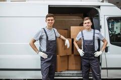 Dos trabajadores sonrientes hermosos jovenes que llevan los uniformes se están colocando al lado de la furgoneta por completo de  imagen de archivo libre de regalías