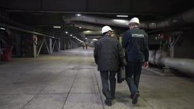 Dos trabajadores van en f?brica Ingenieros en pasillo de la producci?n almacen de video