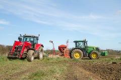 Dos tractores modernos parquearon para arriba después de semilla de la perforación en campo Fotos de archivo libres de regalías