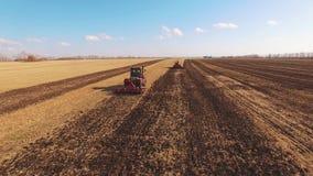 Dos tractores rojos aran el campo almacen de video
