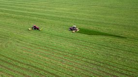 Dos tractores siegan la hierba en una opinión aérea del campo verde foto de archivo libre de regalías