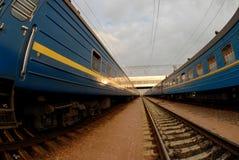 Dos trenes con los carros azules y entre ellos carriles Imagenes de archivo