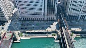 Dos trenes del EL de Chicago que cruzan el río Chicago sobre el puente de la calle de Wells el mañana de la primavera almacen de metraje de vídeo