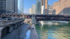 Dos trenes elevados del 'EL 'cruzan el río Chicago, que se inunda sobre el riverwalk después de una tormenta de la primavera