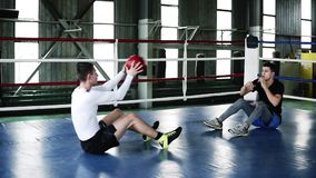 Dos trenes musculares de los hombres en el gimnasio juntos que hace los pectorales para el abdomen y que lanza la bola juguetona  almacen de metraje de vídeo