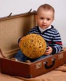 Dos, tres años del bebé llevan la maleta grande aislada en un w Imagenes de archivo