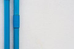 Dos tubos azules del PVC en el muro de cemento blanco Imagen de archivo libre de regalías
