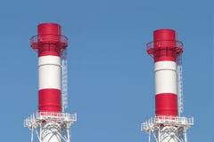 Dos tubos industriales del humo sobre el cielo azul Foto de archivo libre de regalías