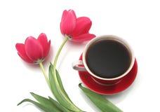Dos tulipanes y tazas rojos del café en una parte posterior del blanco Foto de archivo