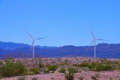 Dos turbinas de viento en el desierto en primavera con montañas y un cielo azul claro imagenes de archivo