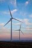 Dos turbinas de viento en la puesta del sol Fotos de archivo