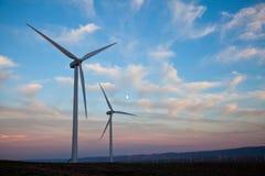 Dos turbinas de viento en la puesta del sol con la luna Foto de archivo