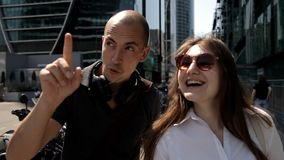 Dos turistas caminan alrededor de la ciudad grande en la calle con los rascacielos y con las porciones de motocicletas parqueadas almacen de video
