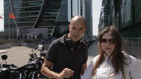 Dos turistas caminan a través de la ciudad grande en la calle con los rascacielos y con muchas motocicletas parqueadas y gozan de almacen de metraje de vídeo