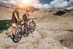 Dos turistas con las bicis exploran la región de la montaña de Himalaya imagen de archivo libre de regalías