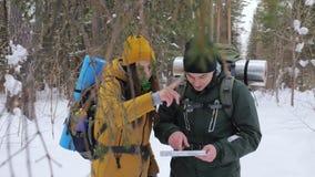 Dos turistas con las mochilas, hombre joven y muchacha, en una mirada nevada del bosque del invierno en un mapa de papel almacen de video