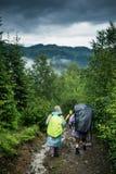 Dos turistas en impermeable caminan a la montaña en la niebla Fotos de archivo libres de regalías