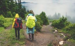 Dos turistas en impermeable caminan a la montaña en la niebla Fotografía de archivo libre de regalías