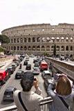 Dos turistas fotografían el Colosseum Abajo usted ve el camino con tráfico de coche y dos furgonetas rojas fotografía de archivo libre de regalías