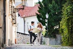 Dos turistas jovenes con el mapa en la ciudad vieja Imágenes de archivo libres de regalías