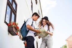 Dos turistas jovenes con el mapa y la cámara en la ciudad vieja Imagen de archivo libre de regalías