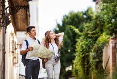 Dos turistas jovenes con el mapa y la cámara en la ciudad vieja Imágenes de archivo libres de regalías
