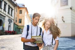 Dos turistas jovenes con el mapa y la cámara en la ciudad vieja Imagen de archivo