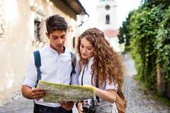 Dos turistas jovenes con el mapa y la cámara en la ciudad vieja Fotos de archivo