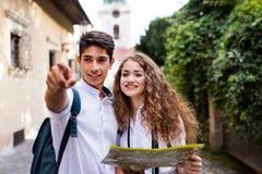 Dos turistas jovenes con el mapa y la cámara en la ciudad vieja Imagenes de archivo