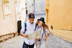 Dos turistas jovenes con el mapa y la cámara en la ciudad vieja Foto de archivo libre de regalías