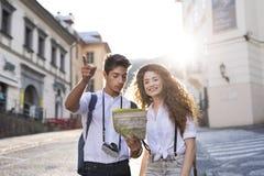 Dos turistas jovenes con el mapa y la cámara en la ciudad vieja Fotos de archivo libres de regalías