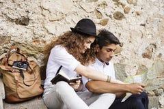 Dos turistas jovenes con un mapa en la ciudad vieja Imagen de archivo libre de regalías