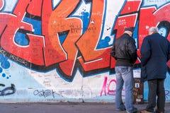 Dos turistas masculinos que admiran las ilustraciones en la galería de la zona este, imagen de archivo libre de regalías