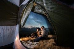 Dos turistas masculinos tienen un resto en acampar en las montañas en la noche debajo del cielo nocturno por completo de estrella foto de archivo
