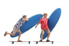 Dos turistas mayores con las tablas hawaianas que montan longboards Imagen de archivo