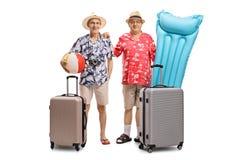 Dos turistas mayores con una pelota de playa, un colchón de aire y el traje Foto de archivo