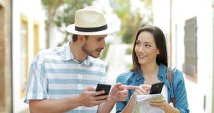 Dos turistas que comprueban sus teléfonos elegantes en la calle metrajes