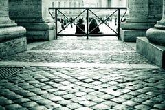 Dos turistas que se sientan entre las columnas Fotos de archivo libres de regalías