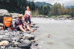 Dos turistas restauran cerca del río de la montaña Foto de archivo