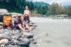 Dos turistas restauran cerca del río de la montaña Imagenes de archivo