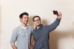 Dos usted los hombres está haciendo un autorretrato con un teléfono móvil fotos de archivo libres de regalías