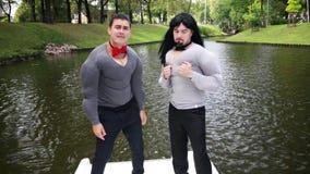 Dos varones caucásicos en camisas rellenadas músculo falso bailan y cantan en barco flotante almacen de metraje de vídeo